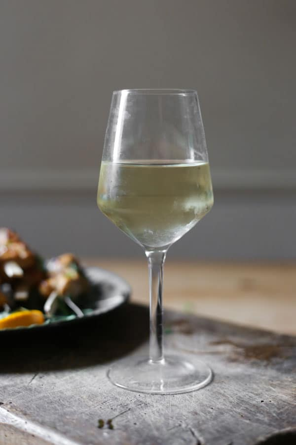 glass of wine on a wooden board next to a plate of food