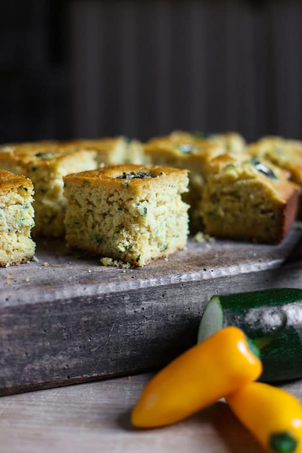 Jalapeno Honey Courgette Cornbread on a wooden board with a knife next to courgette and jalapenos