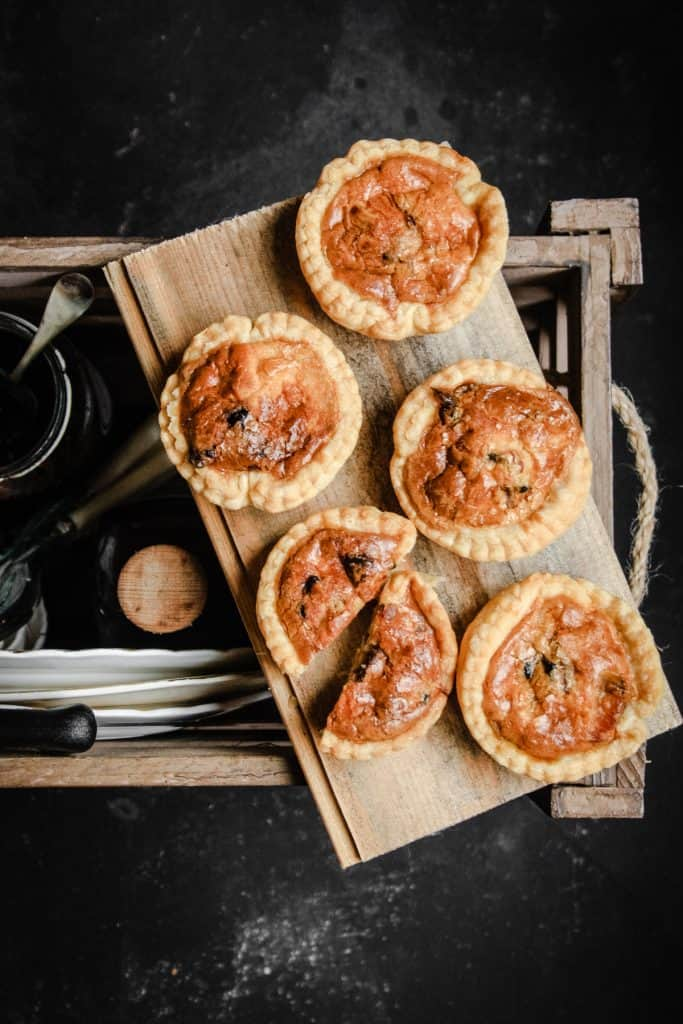 Tartlets on a board balanced on a picnic box with plates and picnicware