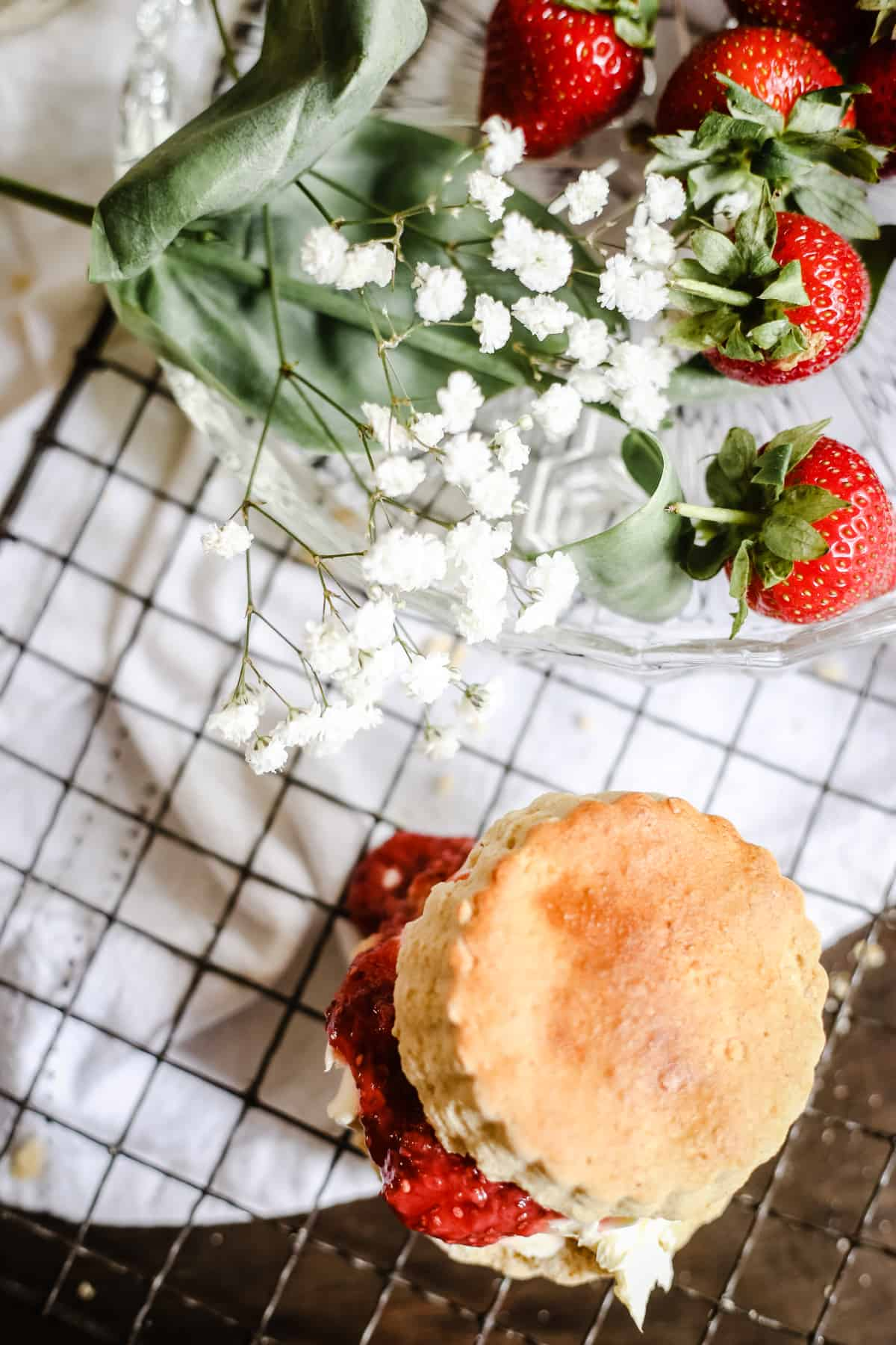 Overhead shot of a gluten-free scone with clotted cream and strawberry jam on a wire rack with a plate of strawberries and flowers