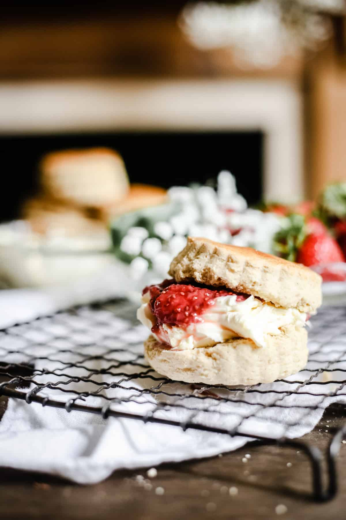 Side shot of a gluten-free scone filled with clotted cream and strawberry jam on a wire rack