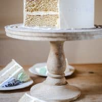 Best Gluten-Free Vanilla Cake on a cake stand on a wooden table