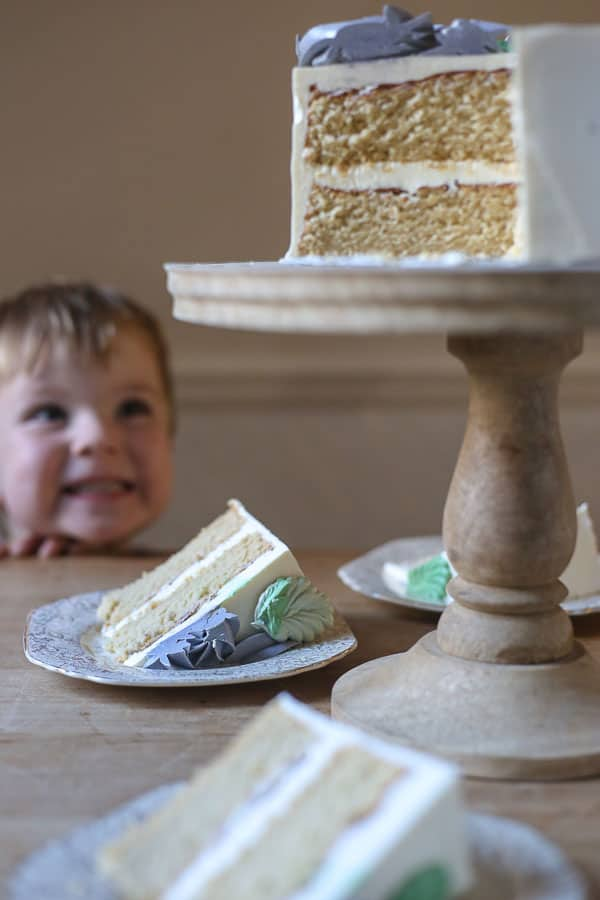 Best Gluten-Free Vanilla Cake on a cake stand on a wooden table with little boy in background