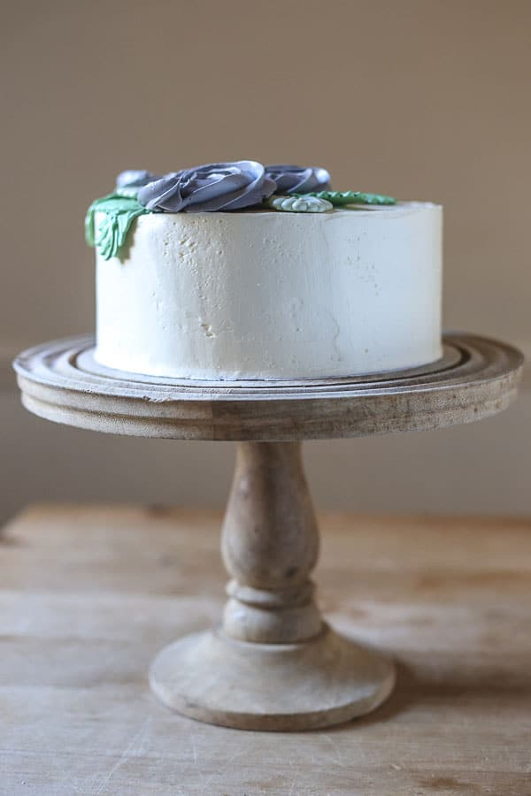 Side view of Best Gluten-Free Vanilla Cake on a cake stand on a wooden table