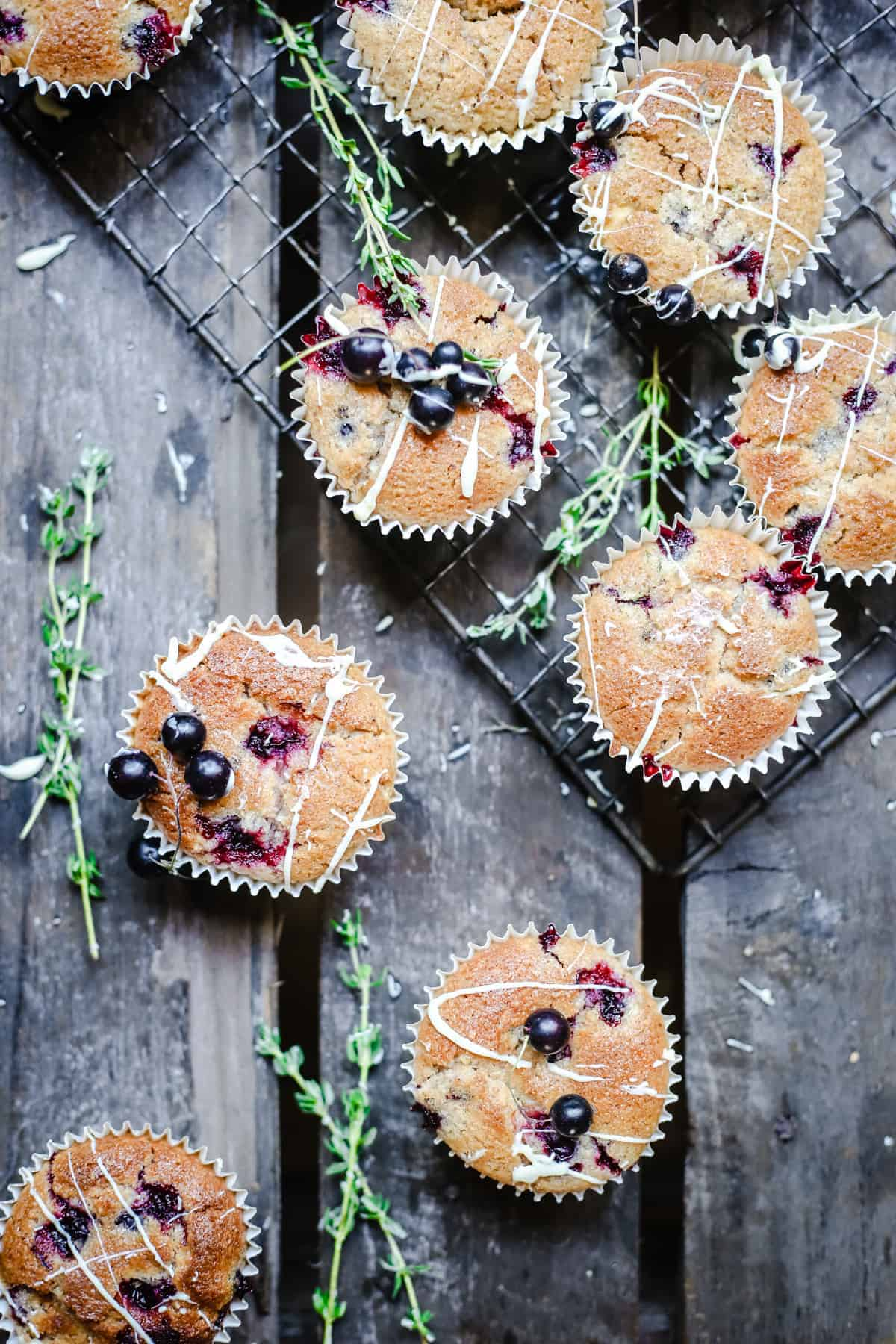 overhead of Blackcurrant White Chocolate and Thyme Muffins on a wooden table
