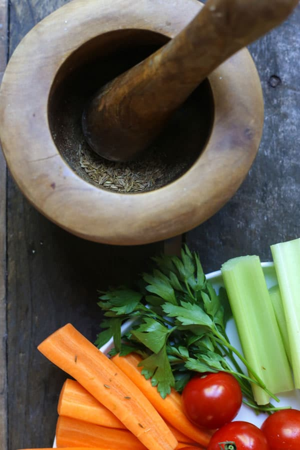 A pestle and mortar filled with cumin seeds next to a plate of crudites