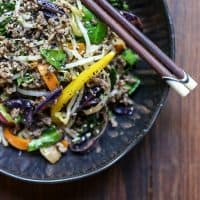 Sriracha Honey Beef Stir Fry in a bowl on a table with chopsticks
