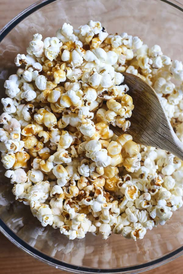 A mixing bowl of Buttered Maple and Bacon Salt Popcorn with a wooden spoon