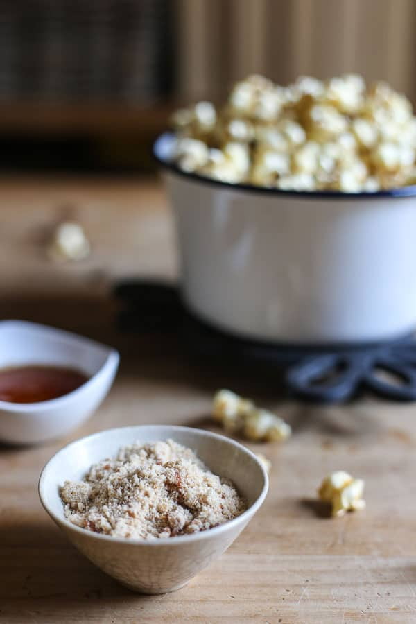 Buttered Maple and Bacon Salt Popcorn in a saucepan on a table with maple syrup and bacon salt