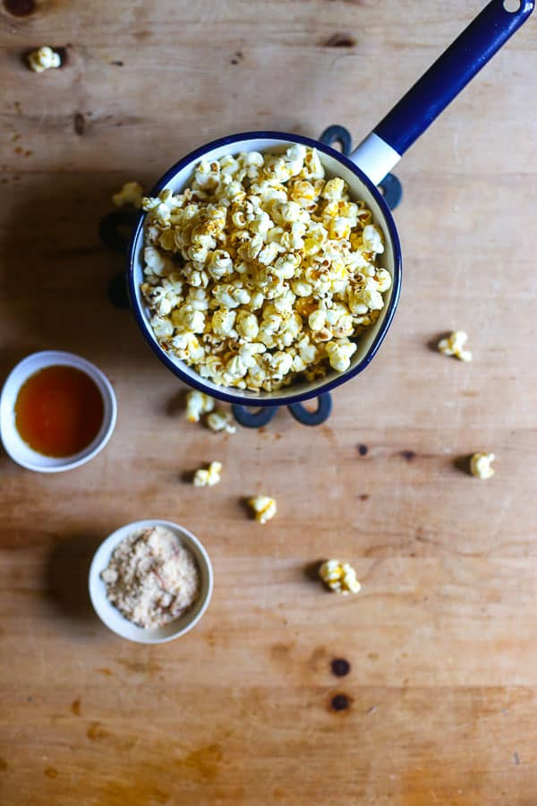 overhead shot of Buttered Maple and Bacon Salt Popcorn in a saucepan on a table with maple syrup and bacon salt