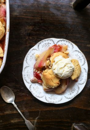 overhead shot of a plate of plum nectarine cornbread cobbler on a table next to a spoon