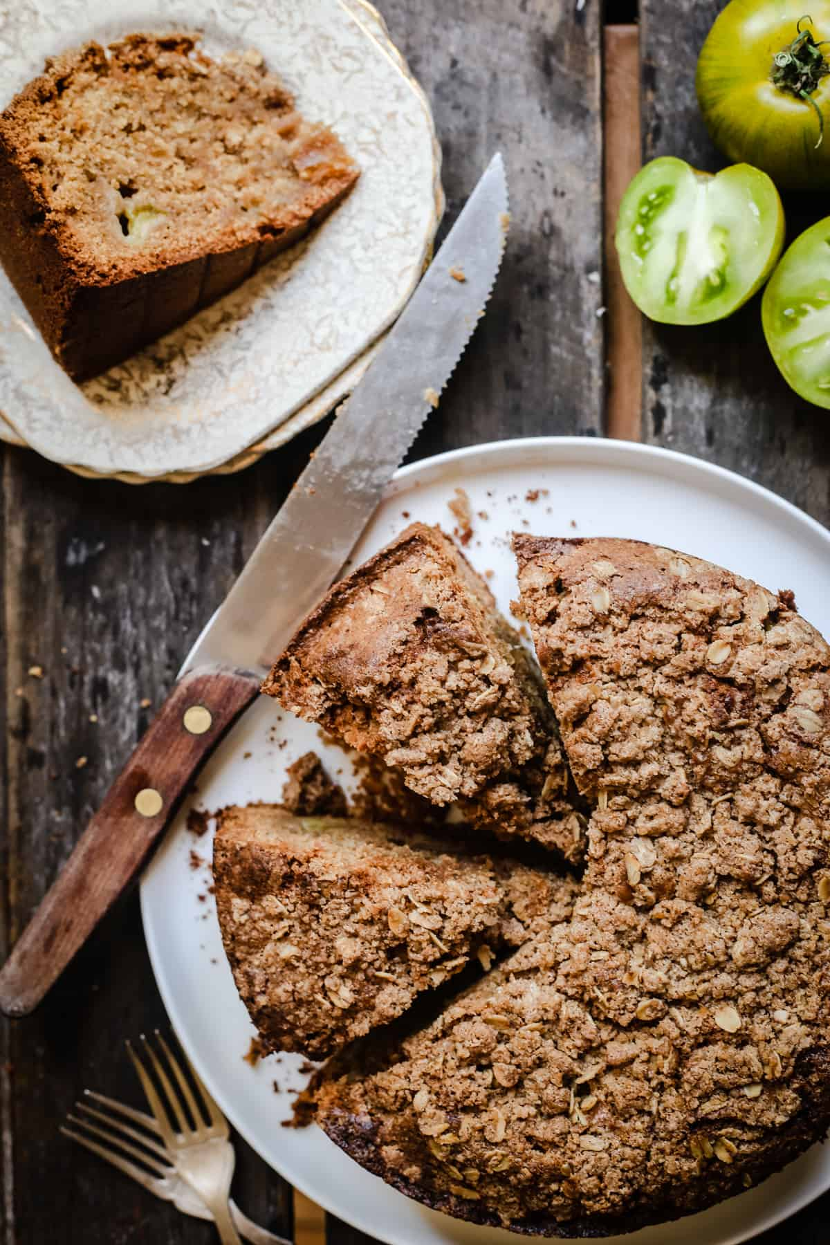 overhead shot of Green Tomato and Stem Ginger Cake with Streusel Topping {gluten-free} on a plate with green tomatoes next to it