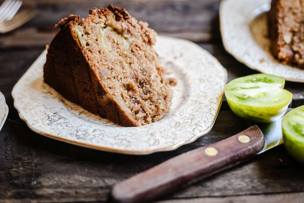 side shot of a slice of Green Tomato and Stem Ginger Cake with Streusel Topping {gluten-free} on a plate with green tomatoes next to it