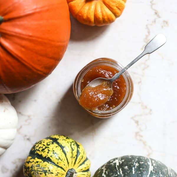 overhead shot of pumpkin jam with a spoon in it surrounded by pumpkins