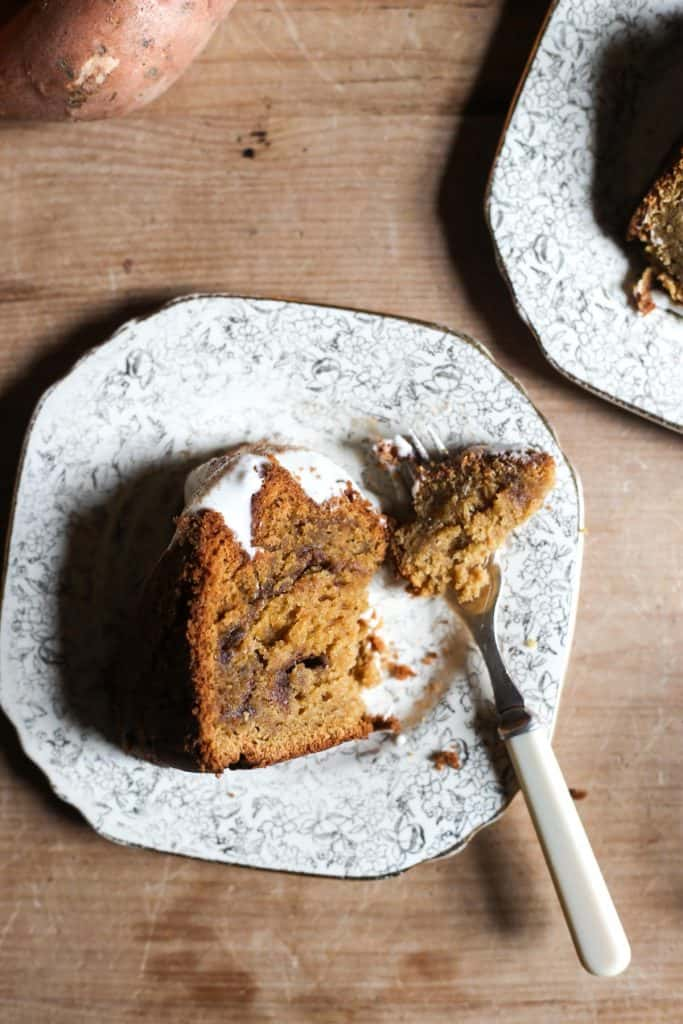 overhead shot of slice of Sweet Potato Cinnamon Swirl Cake on a plate with a sifter and sweet potatoes