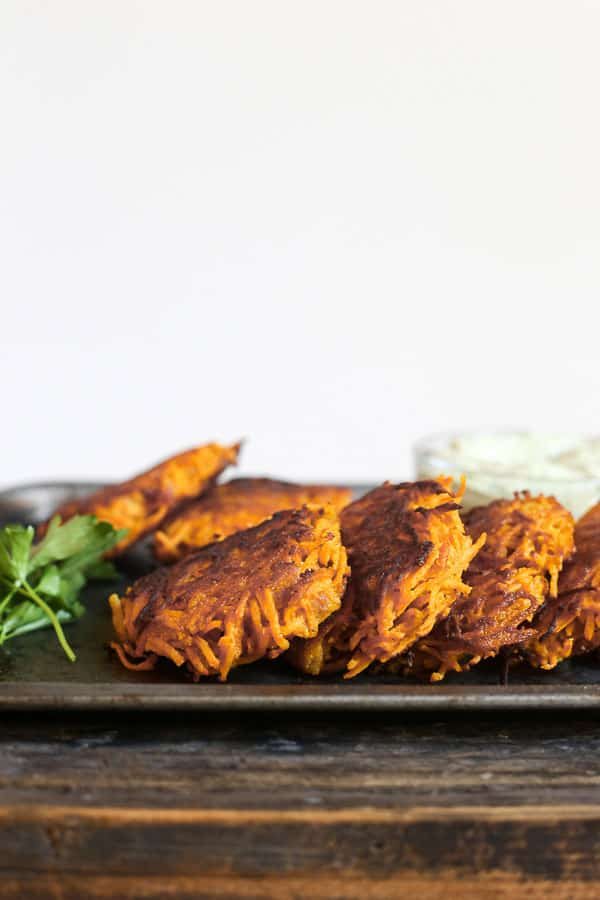 straight on shot of Sweet Potato and Bacon Rosti on a metal tray with tahini sauce