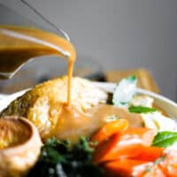 Gluten-Free Gravy being poured out of a gravy boat over a plate of roast chicken and vegetables