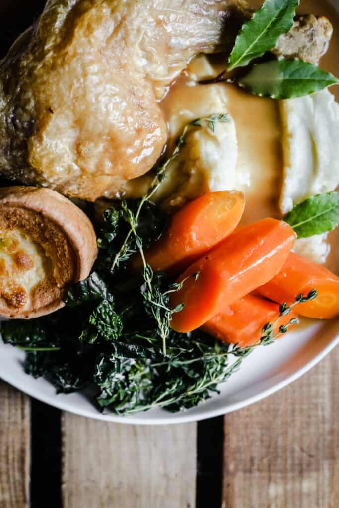 A plate of roast chicken, vegetables and yorkshire pudding with homemade gluten-free gravy