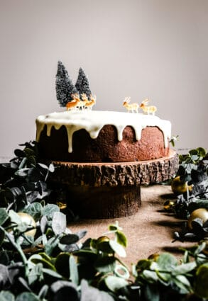 Almond & Mincemeat Christmas Sponge Cake on a cake stand surrounded by greenery