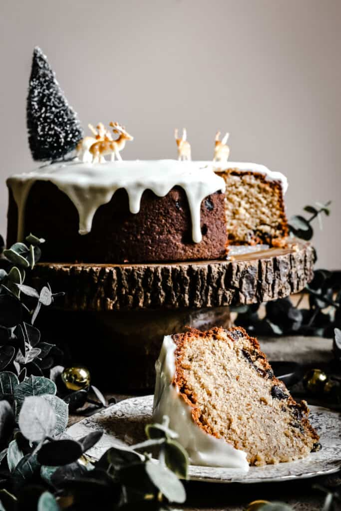 Close up of a slice of Almond & Mincemeat Christmas Sponge Cake on a plate with the whole cake behind