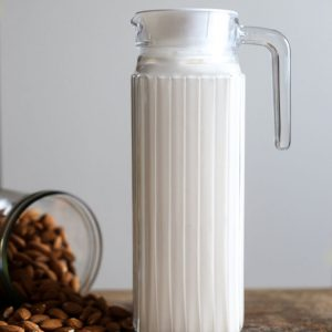 A jug of Homemade Almond Milk next to some almonds