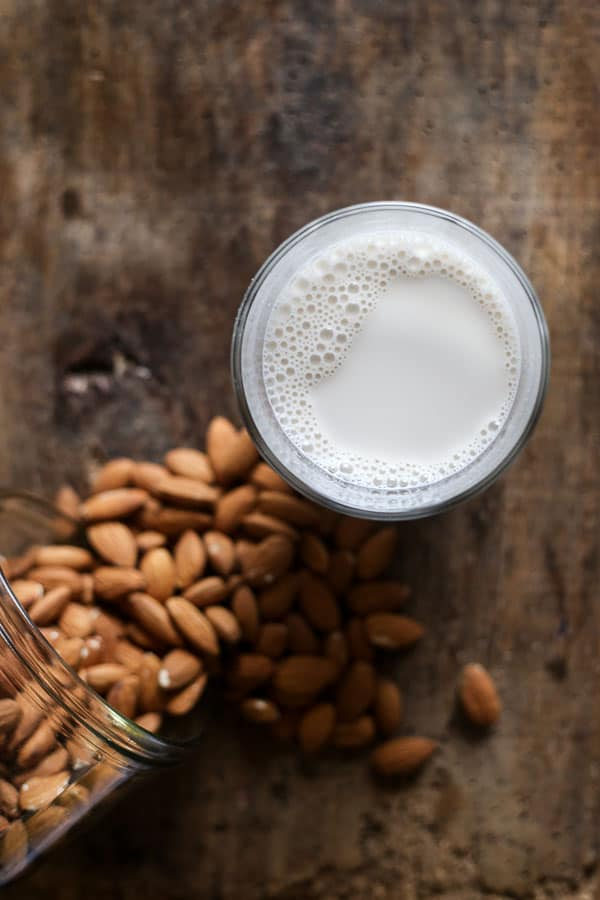 overview of a jug of Homemade Almond Milk next to some almonds