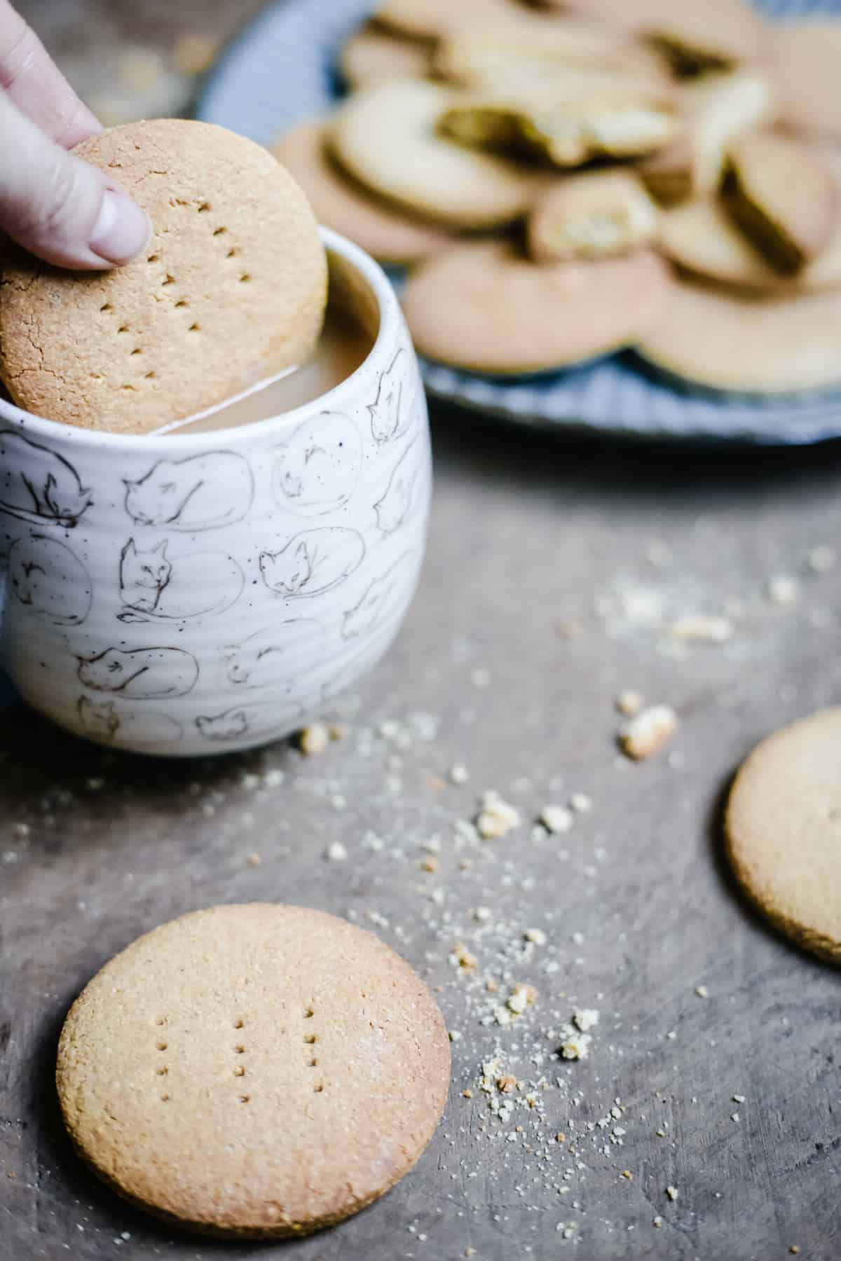 hand dunking a gluten-free digestive biscuit into a mug of tea next to a plate of biscuits