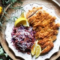 overhead view of Plate of Gluten-Free Chicken Schnitzel with coleslaw and lemon