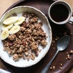 overhead view of a bowl of granola with almond milk, banana slices on a wooden plate with a cup of coffee and a spoon