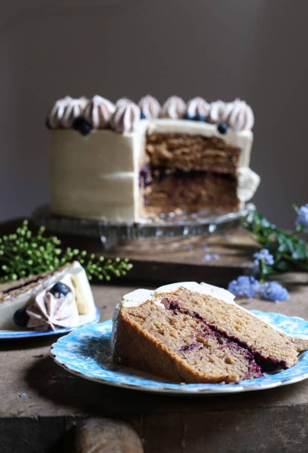 A slice of Apple Blueberry Maple Cake on a plate in front of the cake