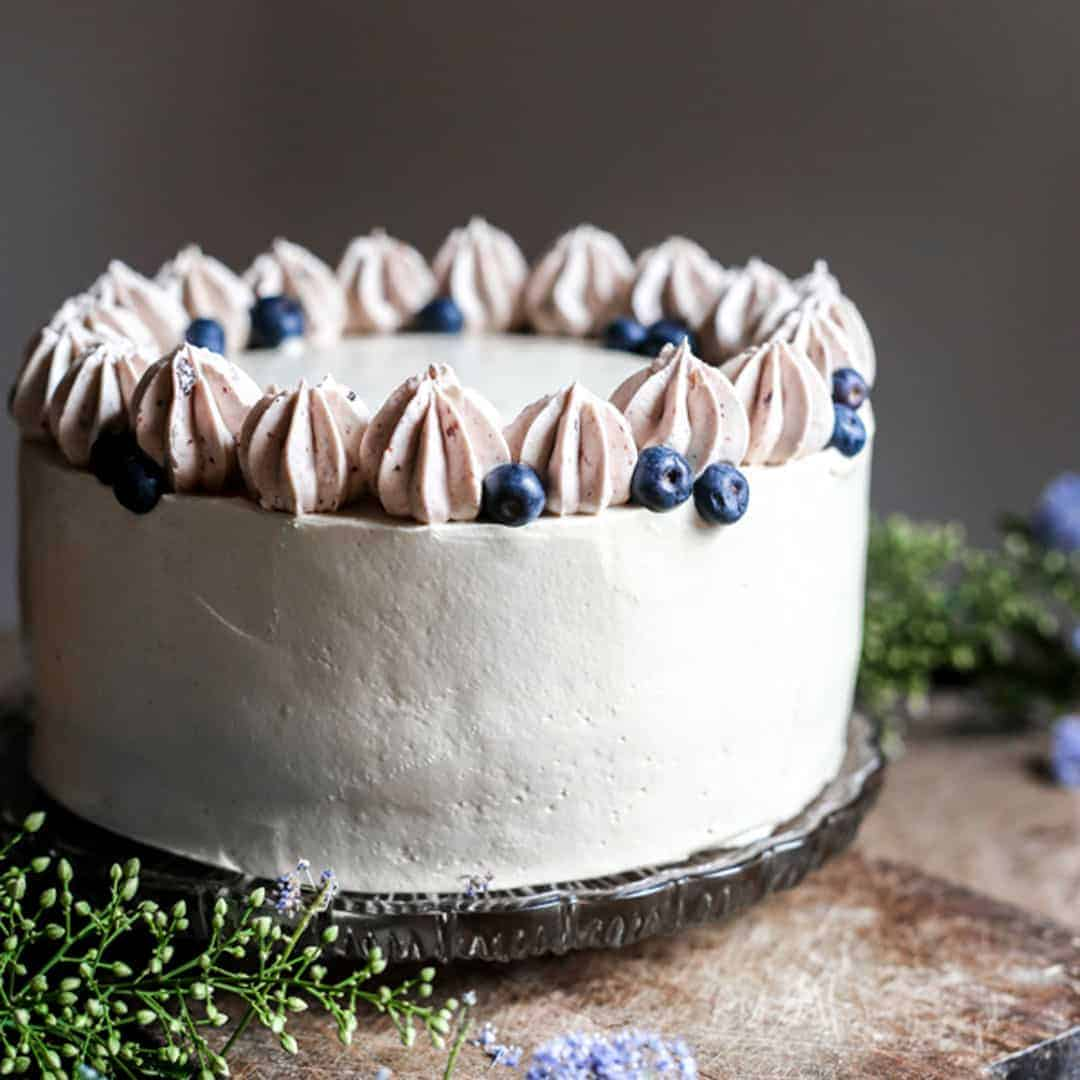 Apple Blueberry Maple Cake on a wooden board surrounded by flowers