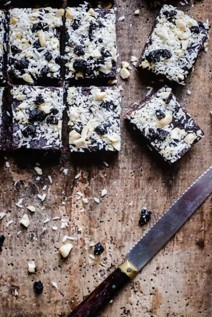 over head shot of Healthy Coconut & Blueberry Bars next to a knife on a wooden board