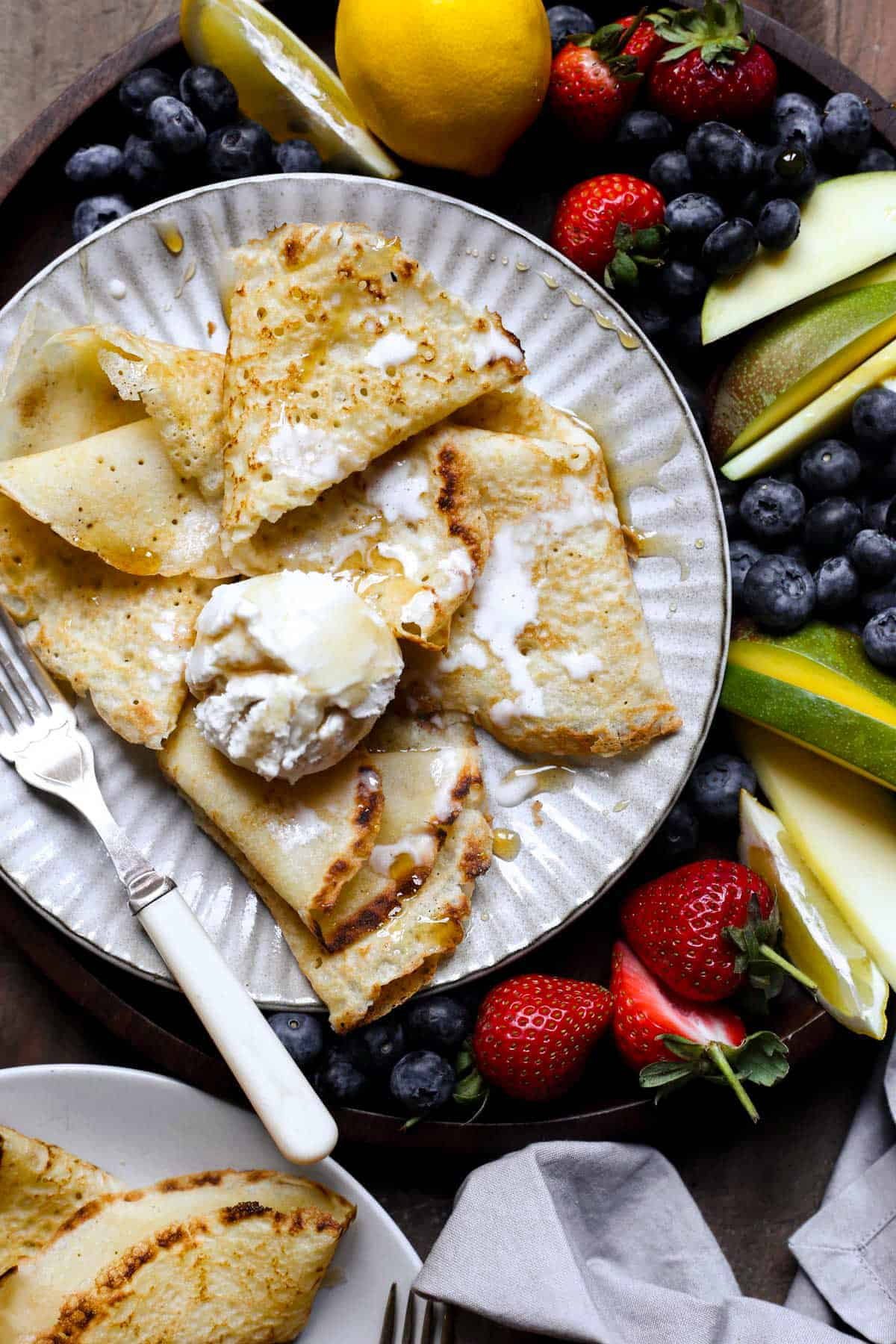A plate of pancakes with ice cream, maple syrup and a fruit platter