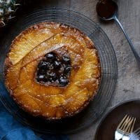 Overhead of Gluten-Free Pineapple Upside Down Cake with a pineapple and glass of caramel next to it.