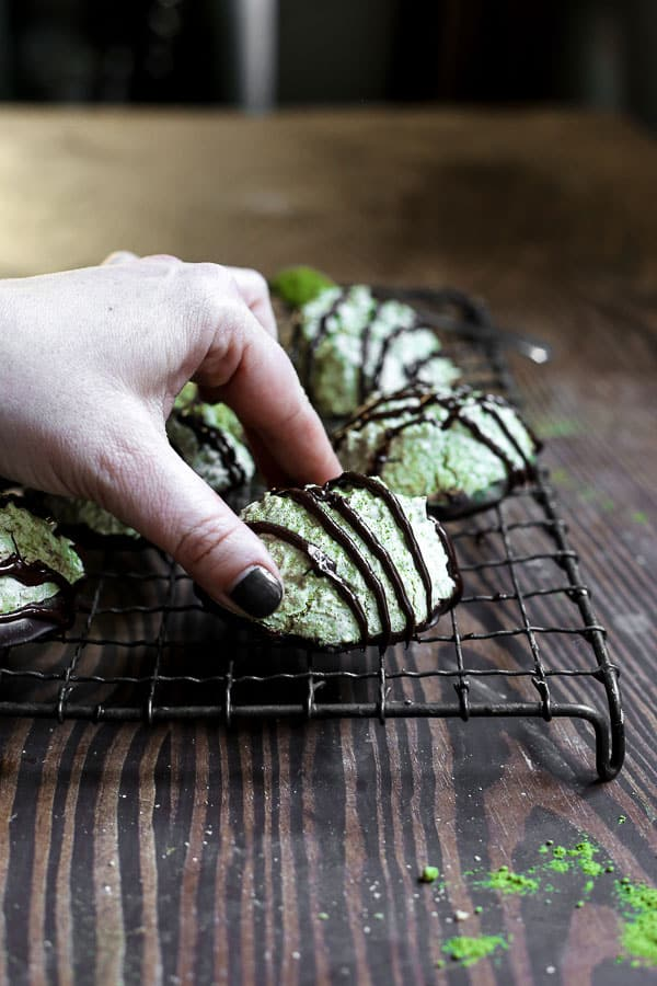 Coconut Matcha Macaroons on a wire rack with a hand picking one up