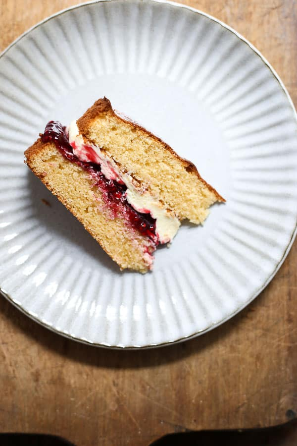 A slice of gluten-free Victoria Sponge cake on a plate on a wooden board