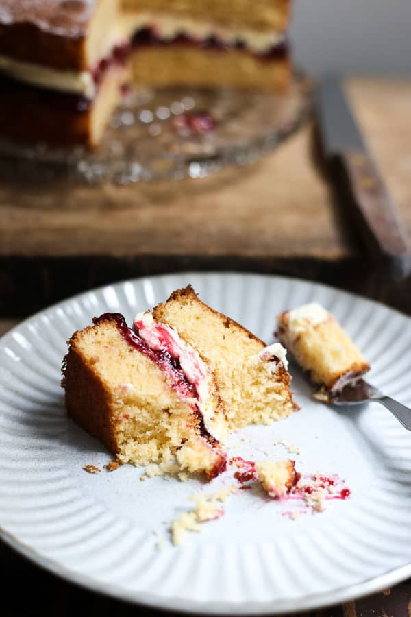 A slice of gluten-free Victoria Sponge cake on a plate with a bite taken out on a wooden board