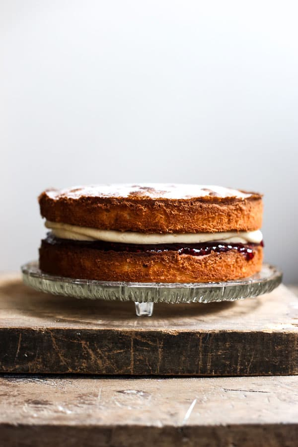 A gluten-free Victoria Sponge Cake on a glass cake stand on a wooden board