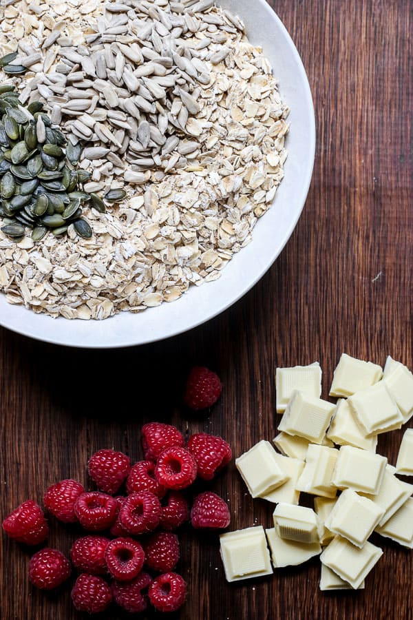 Bowl of oats and seeds next to raspberries and white chocolate