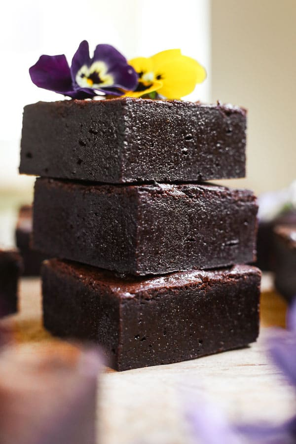 A stack of almond flour brownies with a flower on top.