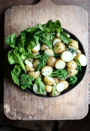 overhead view of a bowl of English Mint Potato Salad on a wooden board
