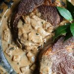 Two steaks in a pan with dairy-free peppercorn sauce