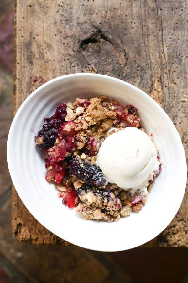 A bowl of apple and blackberry crumble with a scoop of vanilla ice cream in a bowl