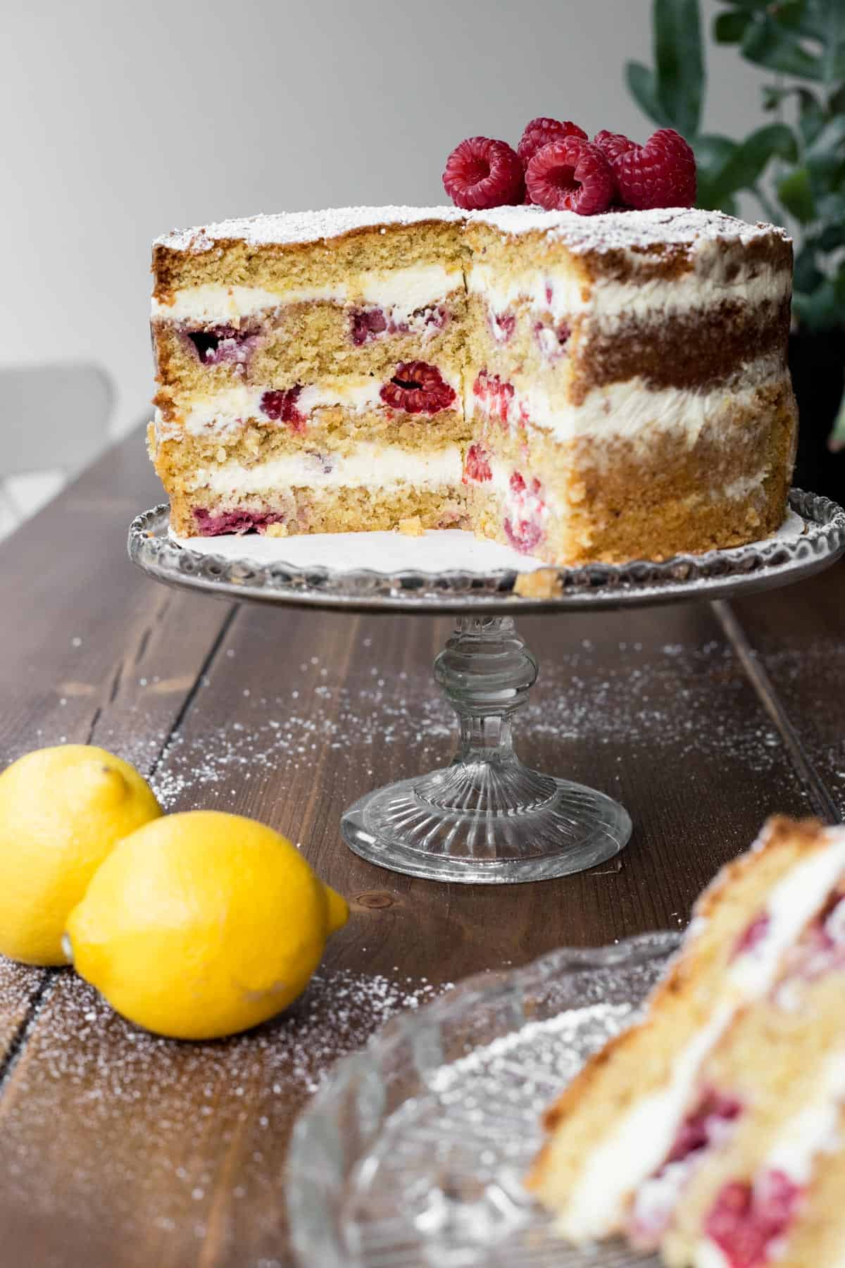 Cut Lemon Raspberry Cake on a cake stand with a slice in front