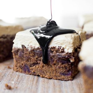 A slice of Sticky Date Cake on a wooden board with a drizzle of black treacle.
