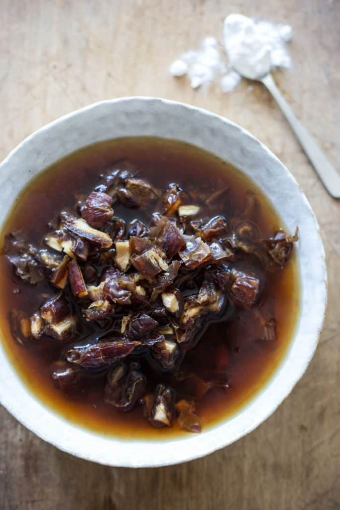 dates soaking in black tea in a white bowl
