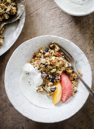 A bowl of Breakfast Quinoa with cashew cream and citrus fruits on a wooden board