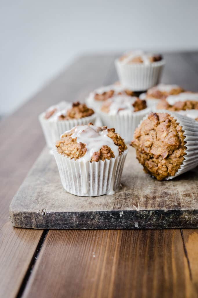 Pumpkin Oatmeal Muffins with maple icing on a wooden board