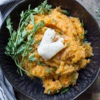 Carrot and Swede Mash in a black bowl on a wooden board
