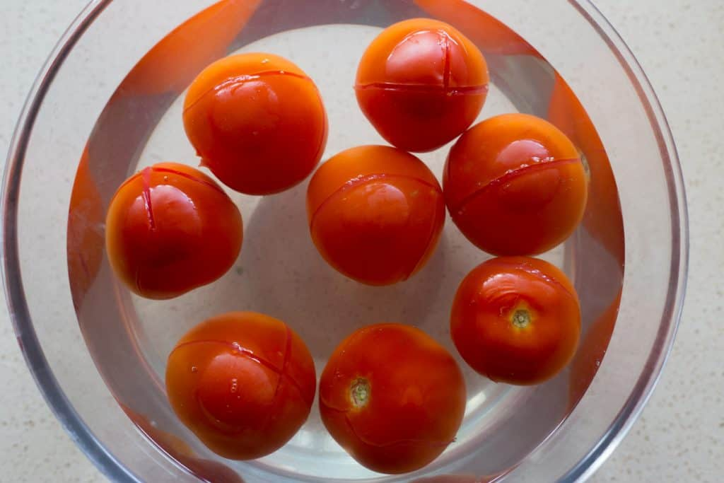 tomatoes in a bowl of boiled water for peeling